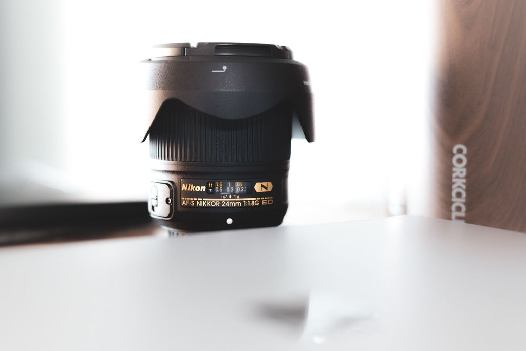 side view of a camera lens facing up on a desk.