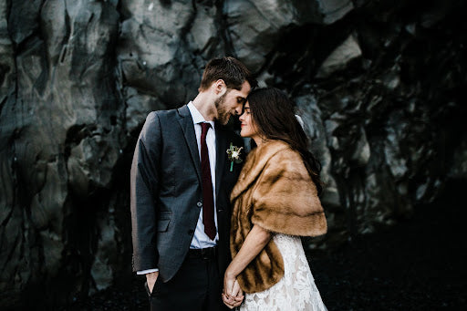 married couple touches foreheads in front of a dark cliff on their wedding day