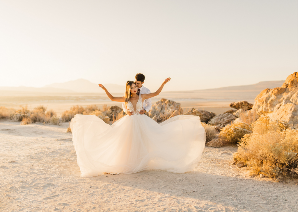 bride standing in front of groom with her hands raised after flaring out the skirt on her dress