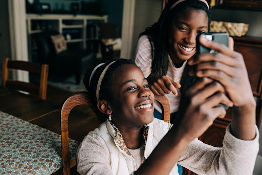 two black teenage sisters smile while taking a selfie in their dining room