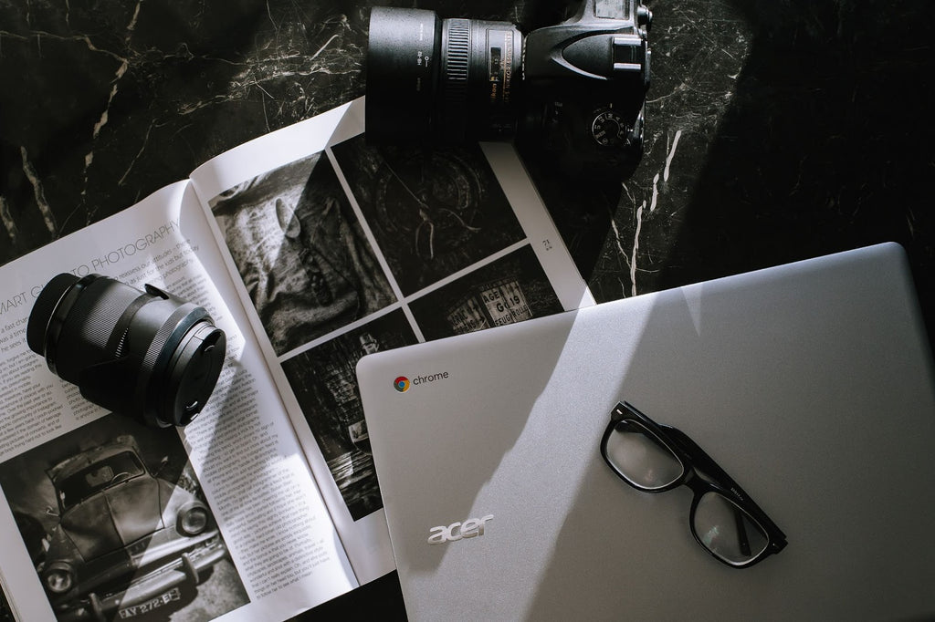 a camera on a tabletop with glasses, a laptop, and a magazine