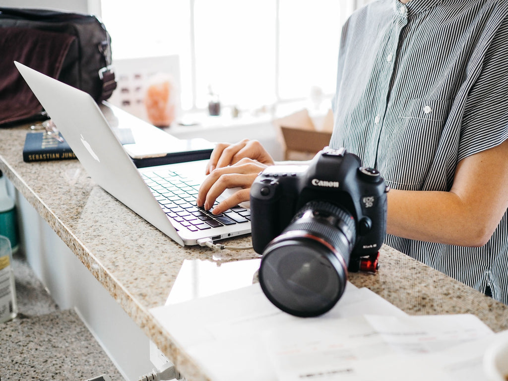 A woman typing on a laptop with a camera sitting beside her, working on starting a photography business.