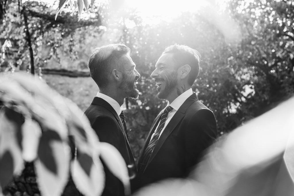 two grooms celebrate their same-sex marriage, smiling at each other in a beautiful sunlit forest