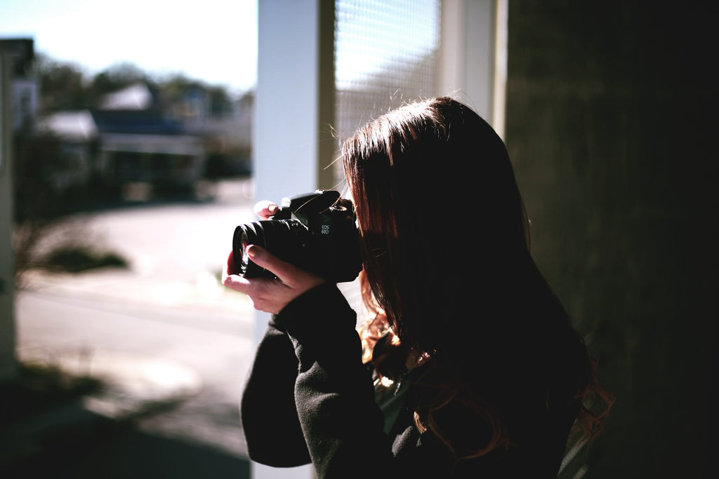 A woman holding a camera thinking about how to start a photography business.