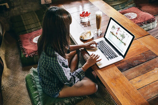 20-something brunette ghostwriter sits cross legged on a green cushion at a low table with a snack and a milkshake writing a photography blog on her laptop.
