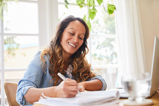 A smiling woman holding a white pen writing for a photography blog in a notebook with a laptop and glass of water on a round brown table and a large bright window behind her.