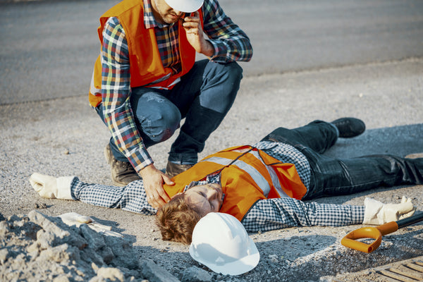 Heat exhaustion recovery: A road worker calls an ambulance to help a coworker who's passed out from the heat