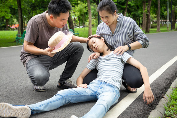 Heat exhaustion recovery: Parents try to help an adolescent who has fainted from the heat