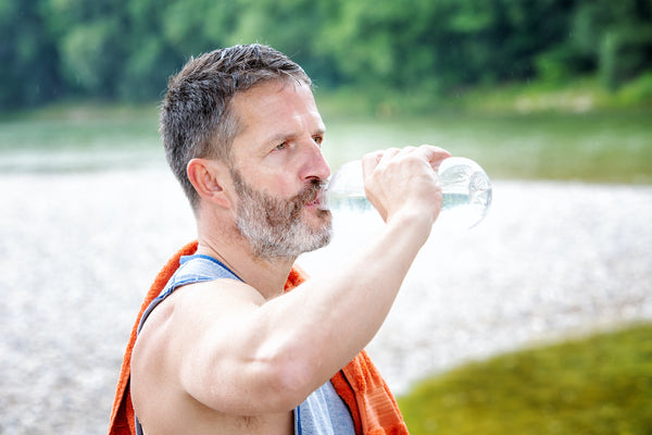 Heat exhaustion recovery: An athlete drinks an oral rehydration solution as he exercises outside