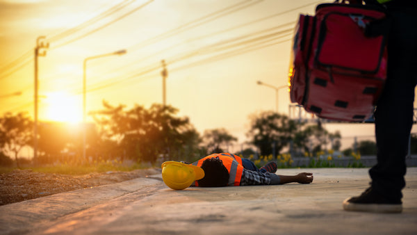 Heat exhaustion symptoms: A road worker passed out on the street on a hot day
