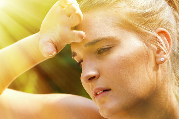 Heat exhaustion symptoms: An athlete holds her hand to her forehead in the heat