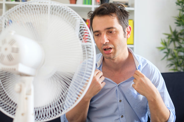 How long does heat exhaustion last: A man cools down in front of a fan