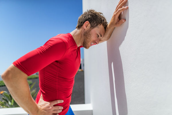 How long does heat exhaustion last: an athlete experience heat exhaustion steadies himself against a wall