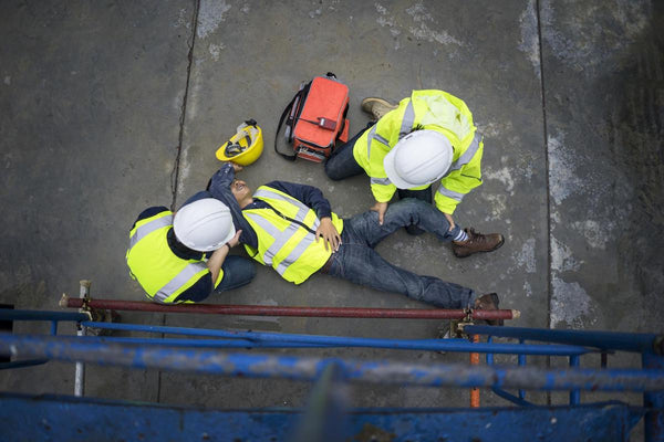 Construction workers help a colleague who has fainted from heat exhaustion