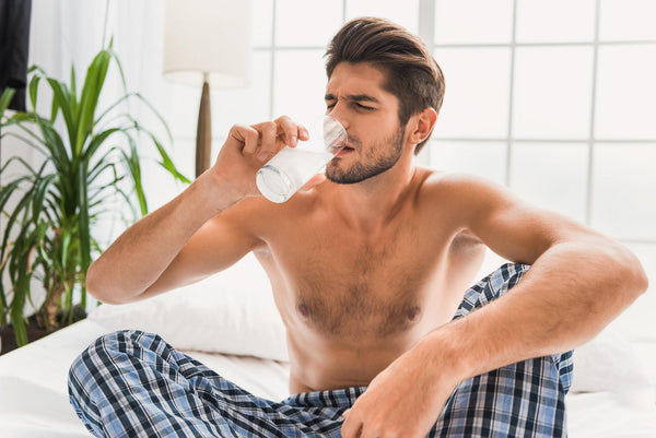 hangover drink: Shirtless man drinking a glass of water