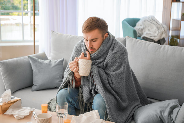 What to drink when sick: A sick man wrapped in a blanket, holding a mug