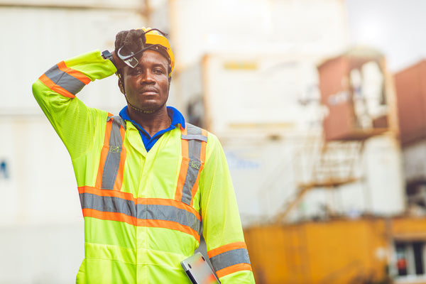 Why do I sweat so much: A dock worker wipes sweat from his brow