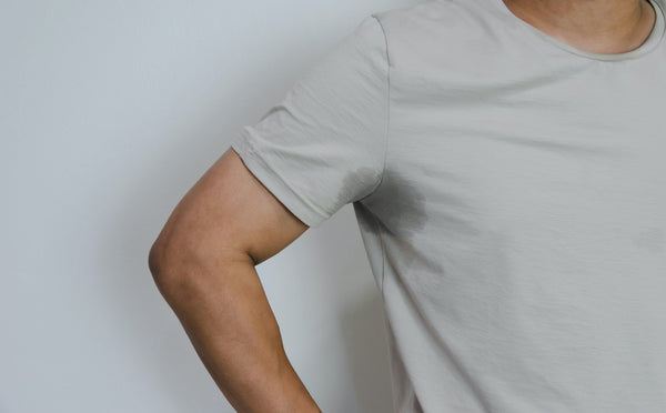 Why do I sweat so much: A man with sweat soaking through the armpit of his shirt