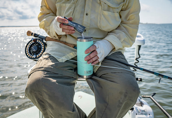 Man on fishing boat pouring electrolytes packet into water container