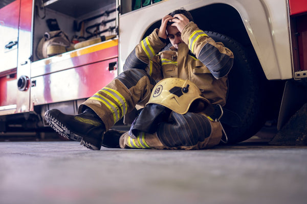 Firefighter sitting and holding his head by a firetruck
