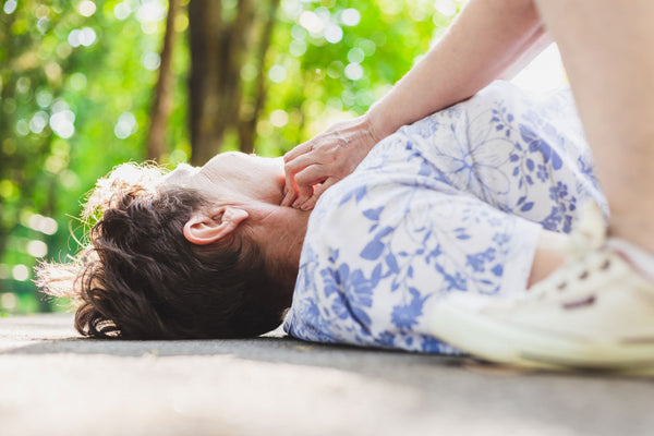 How to tell if you are dehydrated: Elderly person lying on ground having pulse checked