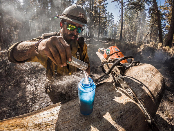 Man pouring electrolyte drink powder in a water bottle