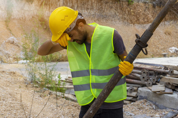 does soda dehydrate you: hard hat worker wiping off sweat