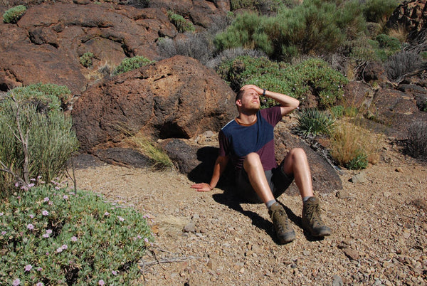 what to do for dehydration: tired man resting on a part of a mountain