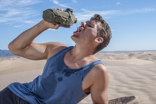 White tongue dehydration: Man drinking water while in the middle of the dessert
