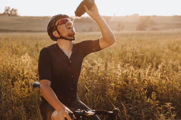 sports drinks: A man drinking while on his bike