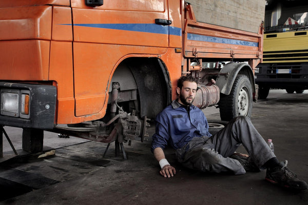 how to stop feeling tired: a man sitting beside a truck while asleep