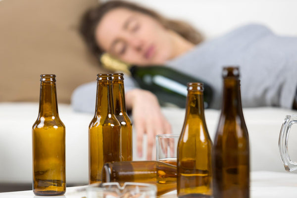 does beer dehydrate you: empty beer bottles on top of beside table of a woman sleeping with a wine bottle
