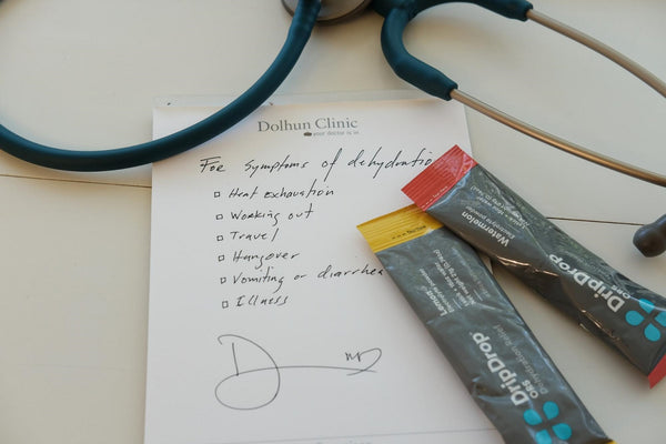 Two DripDrop ORS packs, stethoscope and medical prescription on top of table