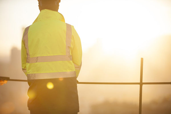 A worker at the construction site looking at sunrise