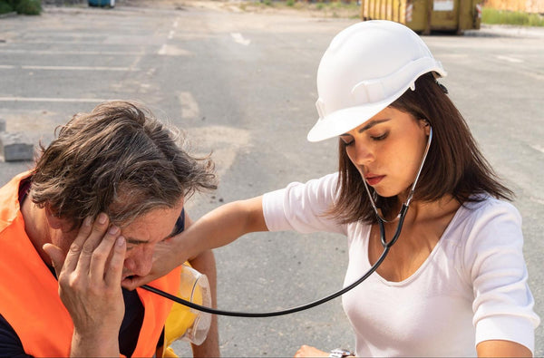 What happens if you don't drink enough water: Paramedic using a stethoscope on a construction worker