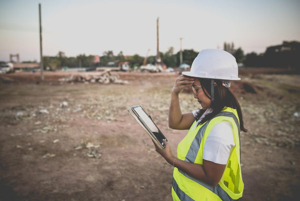 dehydration and anxiety: Woman looking at her tablet in worry while at a construction site