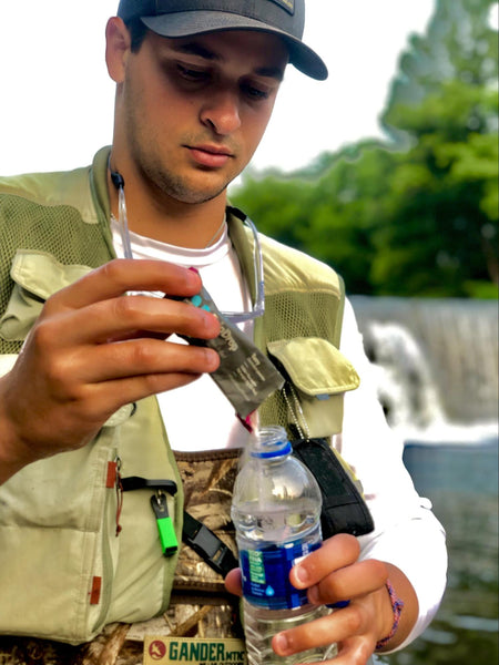 a man adding DripDrop ORS in a water bottle