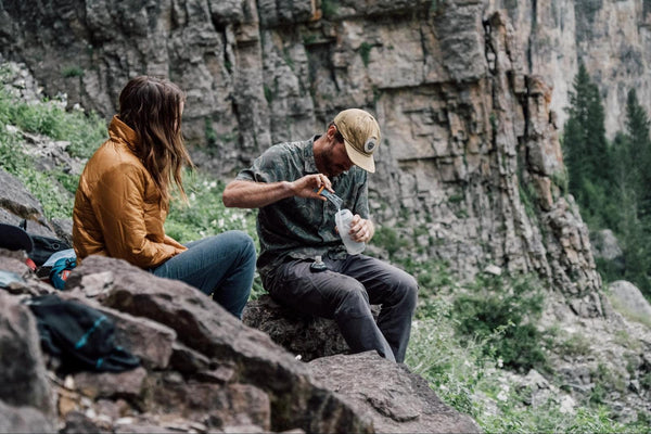 Couple sitting on rock while adding DripDrop ORS to water