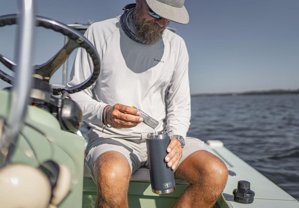 A man on a boat preparing a drink on his bottle