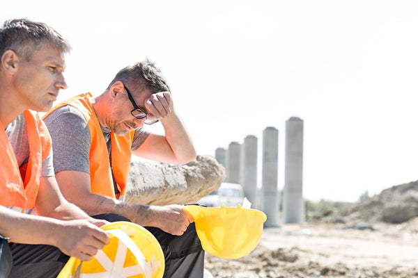 two construction workers sitting outside under the heat of the sun