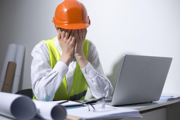 can dehydration cause depression: hard hat worker in an office with his hands on his face