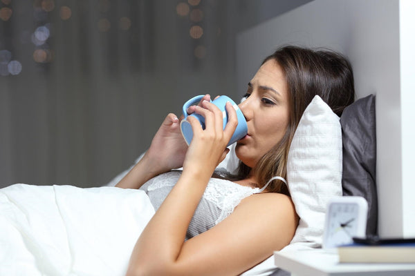 water before bed: Woman drinking water in bed