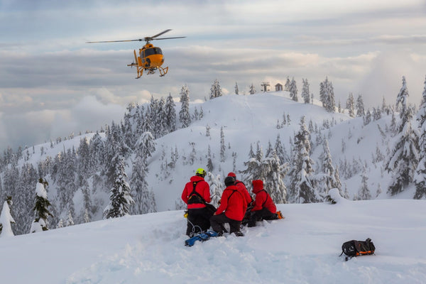 winter dehydration: EMTs tending to a patient in the snow while waiting for the rescue chopper to arrive