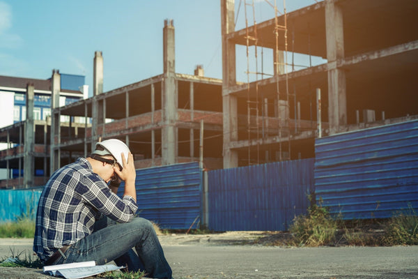 dehydration and anxiety: Stressed engineer sitting with his head on his hands at a construction site