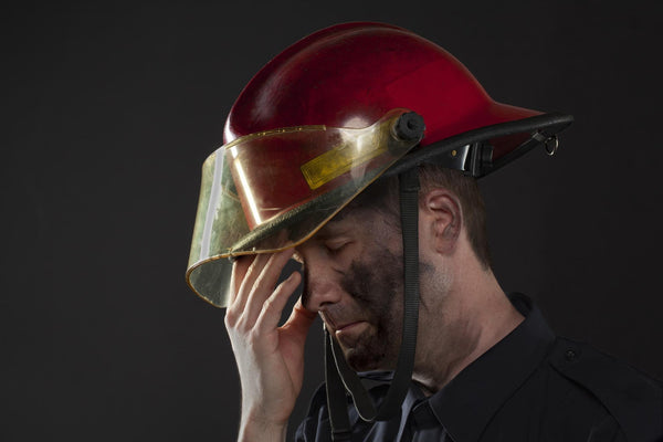 what to do for dehydration: tired fireman touching his face