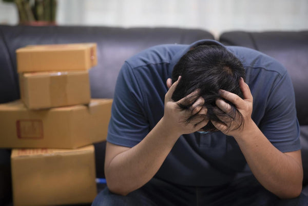 Is alcohol a diuretic: Man experiencing headache sitting on the sofa