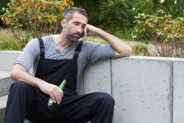does beer dehydrate you: man with eyes closed, sitting on the sidewalk while holding beer