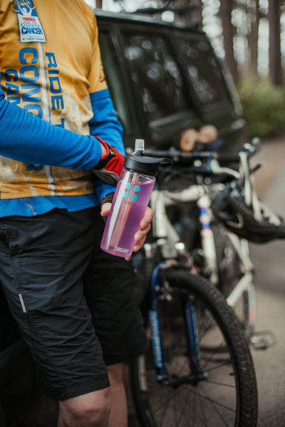 does soda dehydrate you: cyclist with a tumbler full of DripDrop ORS