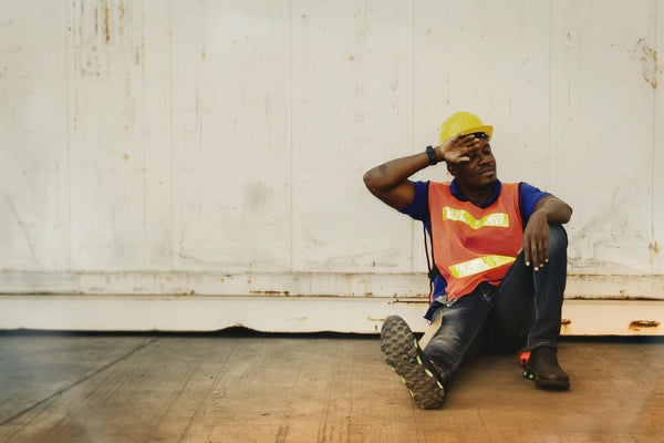 how to stop feeling tired: A construction worker sitting on the floor