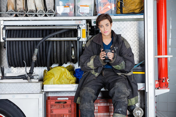 Is coffee a diuretic: Firewoman holding coffee mug while sitting in a truck